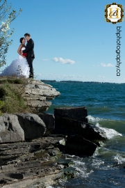 Bride and groom pose on waterfront